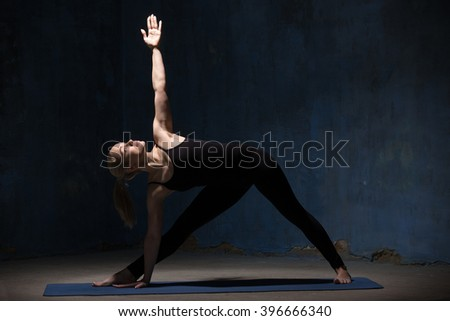 Beautiful sporty fit young woman in black sportswear working out indoors against grunge dark blue wall. Model standing in Utthita Trikonasana, Extended Triangle Pose. Full length - stock photo
