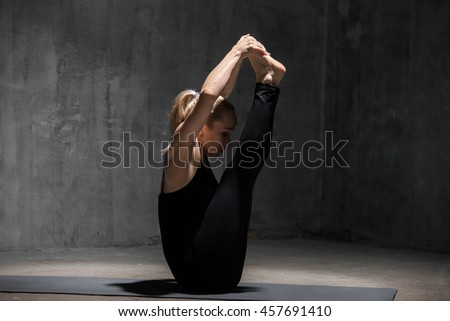 Beautiful sporty fit young woman in black sportswear working out indoors against grunge dark grey wall. Model sitting in Ubhaya Padangusthasana, Both Big Toe posture. Full length