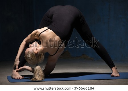 Beautiful sporty fit young woman working out indoors against grunge dark blue wall. Model standing in variation of Wide-Legged Forward Bend Pose, Prasarita Padottanasana. Full length
