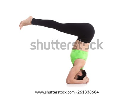 Beautiful sporty girl doing yoga exercises for abdominal muscles, flat belly, supported headstand yoga asana, salamba sirsasana - stock photo