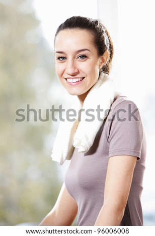 Beautiful sporty girl is smiling and resting in a gym. - stock photo