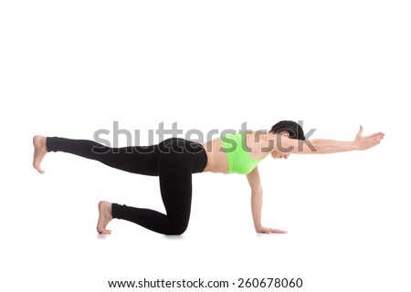 Beautiful sporty girl practices yoga, pilates, doing balance exercise bird dog, kneeling opposite arm and leg extension, asana sunbird (chakravakasana), fitness training for spine and shoulders - stock photo