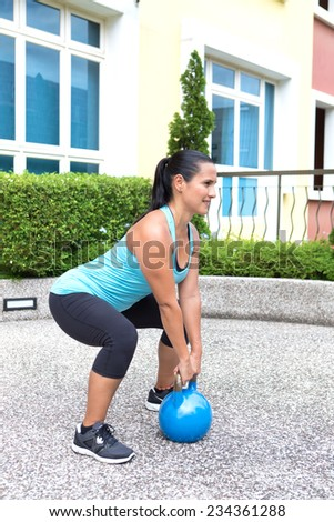 Beautiful sporty hispanic woman in blue training with kettlebell doing dead lift - stock photo