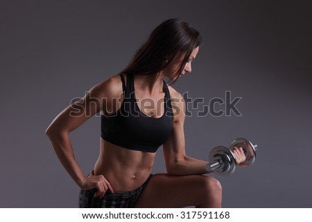 beautiful sporty muscular woman working out with dumbbells - stock photo