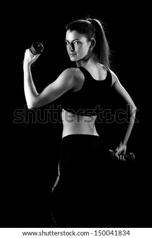 beautiful sporty muscular woman working out with dumbbells . Black and white photo - stock photo
