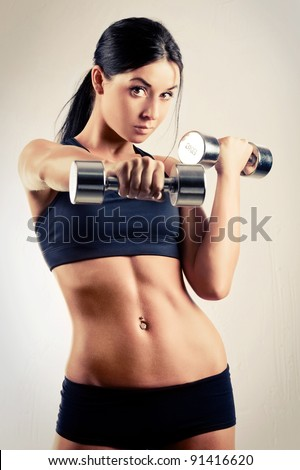 beautiful sporty muscular woman working out with two dumbbells - stock photo