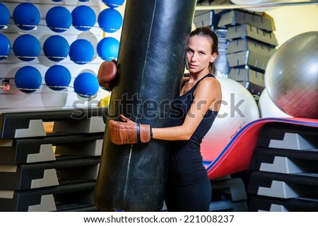 Beautiful sporty woman boxing with red punching bag at gym.