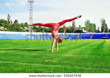 Beautiful sporty woman doing cartwheel on stadium - stock photo