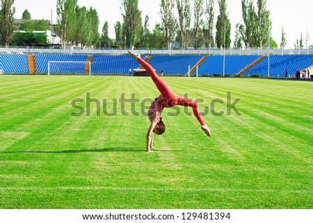 Beautiful sporty woman doing gymnastic exercise on stadium - stock photo