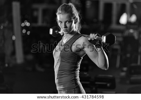 Beautiful sporty woman doing power fitness exercise at sport gym. Girl with dumbbell. Black and white. - stock photo