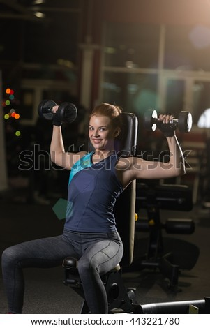 Beautiful sporty woman doing power fitness exercise at sport gym. Girl with dumbbell on black. - stock photo