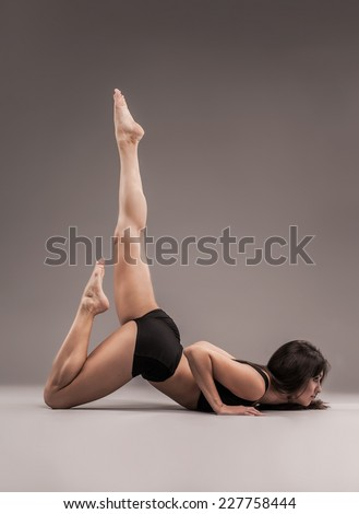Beautiful sporty woman is doing gymnastic exercise  - stock photo