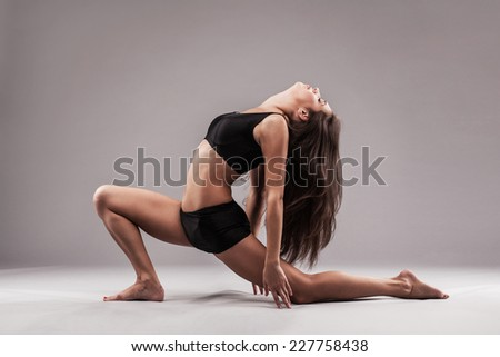 Beautiful sporty woman is doing stretching exercise  - stock photo