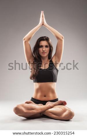 Beautiful sporty woman is doing yoga asana. Lotus pose - stock photo
