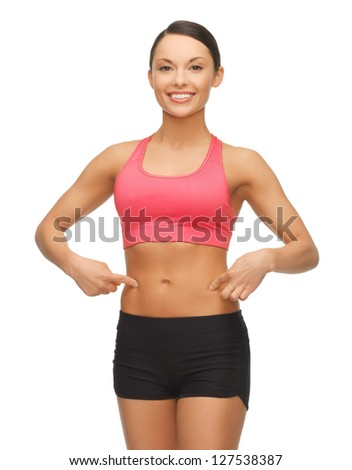 beautiful sporty woman pointing finger on her belly
