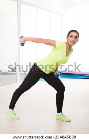 Beautiful sporty woman show exercise with dumbbells in gym - stock photo