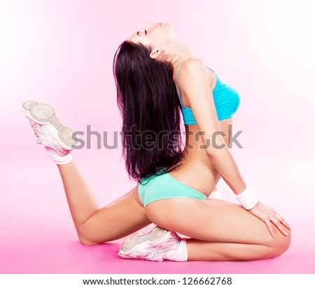 beautiful sporty woman stretching against pink studio background - stock photo