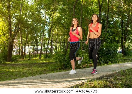 Beautiful sporty women jogging in green park, sunny day