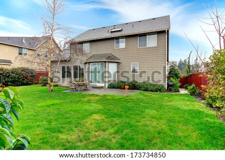 Beautiful spring backyard. Patio with dining table set overlooking green trim and tree - stock photo