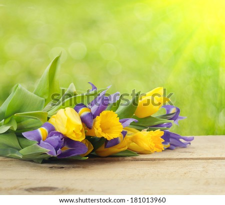 beautiful spring bouquet on wooden table on green background - stock photo