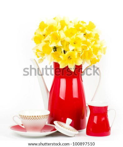 Beautiful spring flowers in a red teapot