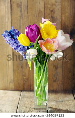 Beautiful spring flowers in glass vase on wooden background