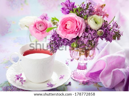 Beautiful spring flowers in vase and cup of tea - stock photo