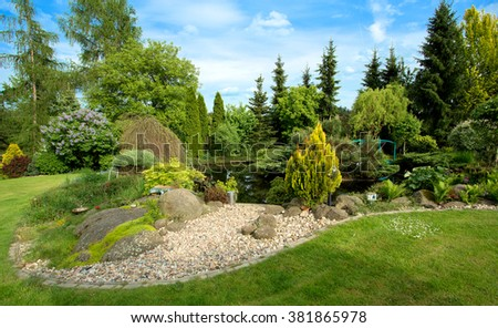 Beautiful spring garden design, with conifer trees, green grass and eneving sun, in backgroung foot bridge over pond - stock photo