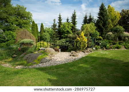 Beautiful Spring Garden Design, With Conifer Trees, Green Grass And Pond