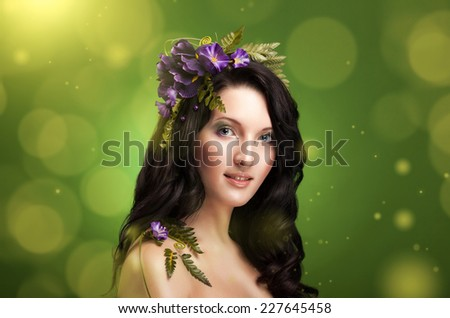 beautiful spring girl image with flowers decoration on a green background - stock photo