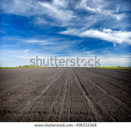 Beautiful spring landscape with plowed field under blue sky with clouds, - stock photo