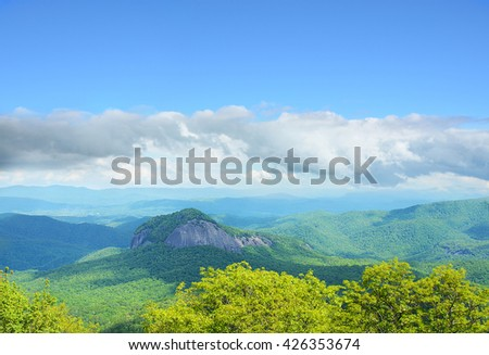 Beautiful spring mountain landscape,Looking Glass Rock and  blue sky with white clouds in the background. Copy space. North Carolina. Blue Ridge Parkway. USA - stock photo