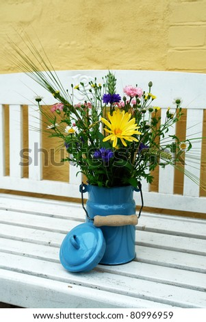Beautiful spring summer flowers in a blue tin bucket on a garden bench vertical image