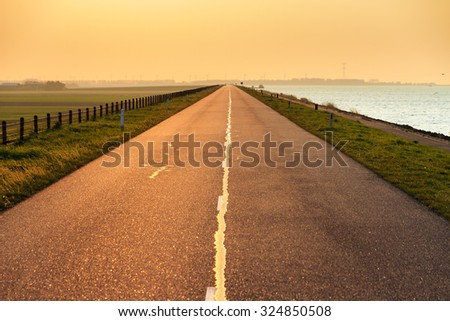 Beautiful spring sunset at the levee with a road to nowhere - stock photo