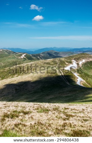 Beautiful spring Ukrainian mountains with remnants of snow and roads under a blue sky - Svydovets range, Carpathians, West Ukraine - stock photo
