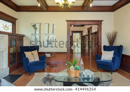 Beautiful staged living room in classic craftsman house with blue chairs and glass table.  - stock photo