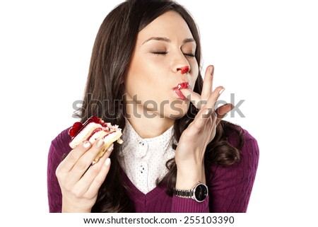 Beautiful stained girl eating cake and licks her fingers - stock photo