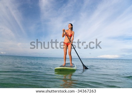 beautiful stand up paddle girl on turquoise waters exercising