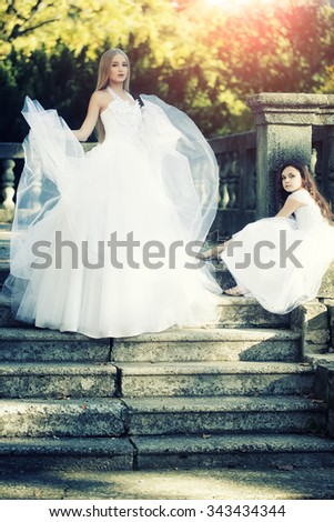 Beautiful standing blonde bride in white tulle lush dress and cute brunette curly little girl in nice gown sitting on grey stone stairs with banister in autumn park, vertical photo - stock photo