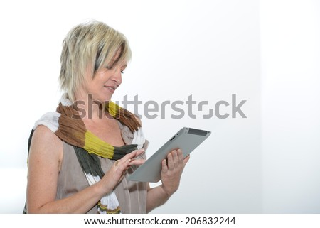 Beautiful standing up blond senior woman working with tablet PC  - stock photo