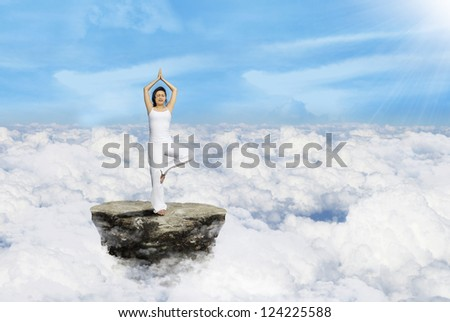 Beautiful standing yoga position by Asian woman above clouds - stock photo