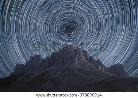 Beautiful star trails over the rocky mountains. Polar North Star at the center of rotation.