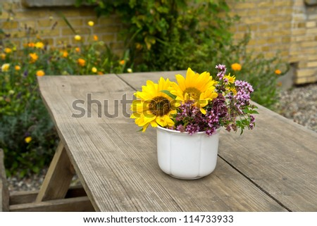 Beautiful still life image vase of vibrant flowers on a garden table