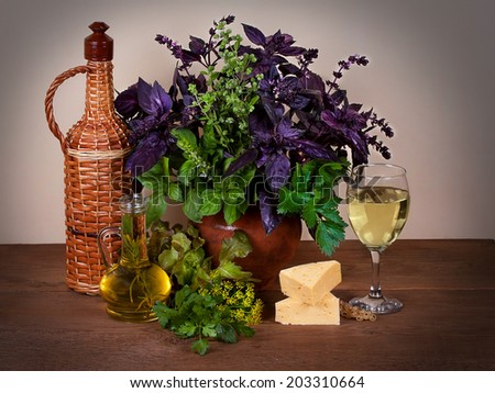 Beautiful still life with basil, celery, dill, marjoram, parsley, lettuce; cheese and wine - stock photo