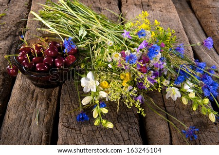 Beautiful still life with cherries and fresh flowers - stock photo