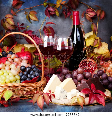 Beautiful still life with wine glasses, grapes, pomegranate and cheese - stock photo