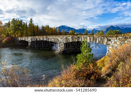 Beautiful stone bridge entering Glacier National Park in Montana from the east entrance with golden vegetation and tall peaks in the background