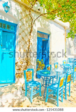 Beautiful stone made road with old traditional houses and traditional iron made blue coffee tables and chairs in Chora the capital of Amorgos island in Greece - stock photo