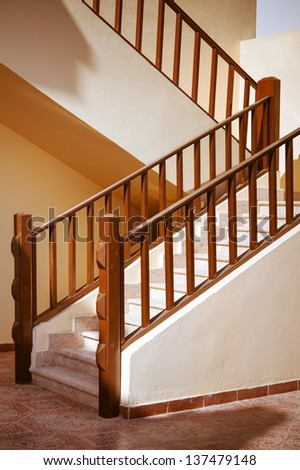 Beautiful stone staircase with wooden banister. - stock photo