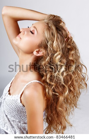 Beautiful strawberry blond teenage girl with long curly hair over grey studio background . - stock photo